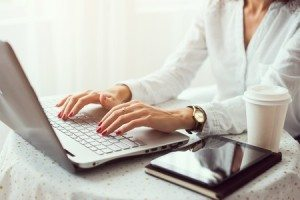 45720671 - woman working in home office hand on keyboard close up